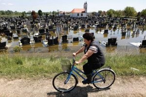 A Bosnian woman cycles past a flooded cemetery in the village of Domaljevac near the Bosnian town of Orasje along the river Sava, 124 miles north of Sarajevo, Bosnia's capital. (AP Photo)