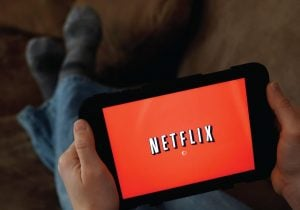 A person displays Netflix on a tablet. (AP Photo)