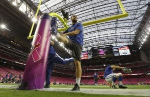 """Indianapolis Colts' quarterback Andrew Luck leans on a goalpost as he stretches before a game against the Houston Texans, Oct. 9, in Houston. The NFL celebrates Breast Cancer Awareness Month by """"pinking"""" stadiums and select equipment. Photo courtesy David Phillips/AP"""