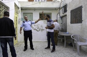 In this photo taken Tuesday, Sept. 30, 2014, Palestinian Mahmoud Qarain, a 30-year-old resident of the east Jerusalem neighborhood of Silwan, argues with Israeli police inside his cousin's home, which has been taken over by Jewish settlers. AP Photo/Mahmoud Illean