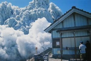 In this Saturday, Sept. 27, 2014 file photo taken by 59-year-old hiker Izumi Noguchi who fell victim to the eruption of Mount Ontake, and was offered to Kyodo News by his wife, Hiromi, Friday, Oct. 3, a hiker standing on the summit shrine compound on Mount Ontake watches dense plumes of gases and ash billowing from the crater as the volcanic mountain starts to erupt. AP Photo/Kyodo News, Izumi Noguchi