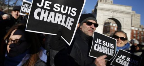 """Attendees hold """"Je suis Charlie"""" (I am Charlie) signs as several hundred people gather in solidarity with victims of two terrorist attacks in Paris on Jan. 10. (Jason Decrow 