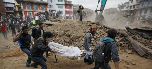 Aid workers rush a victim through the rubble of Kathmandu, Nepal, after a strong earthquake that occurred Saturday, April 25. (AP Photo/ Niranjan Shrestha)