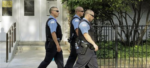 Beat police patrol the streets of Chicago. Many pundits question whether increased police presence is a socially or economically effective method to fight crime. (AP Photos/M. Spencer Green)