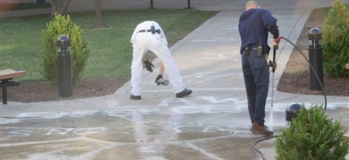 """Chalk outlines and writing is washed away on request by Public Safety after the art display put on by Amnesty International at DePaul was shut down late Tuesday night. The chalk that read """"law enforcement is not above the law"""" was washed away early Wednesday morning."""