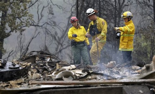 Firefighter Sean Norman, center, and search dog handlers Mary Cablk, left, and Lynne Engelbert look over the remains of a home in the Anderson Springs area of a man missing following a wildfire days earlier Wednesday, Sept. 16, 2015, near Middletown, Calif. Aided by drought, the flames have consumed more than 100 square miles since the fire sped Saturday through rural Lake County, less than 100 miles north of San Francisco. Cooler weather helped crews gain ground and the fire was 30 percent contained Wednesday. (AP Photo/Elaine Thompson)