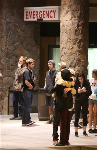 Students embrace outside a hospital emergency room in Flagstaff, Ariz., on Friday, Oct. 9, 2015, after an early morning fight between two groups of college students escalated into gunfire, leaving one person dead and three others wounded, authorities said. The shooting occurred outside a dormitory near the Northern Arizona University campus. (Jake Bacon/Arizona Daily Sun via AP)
