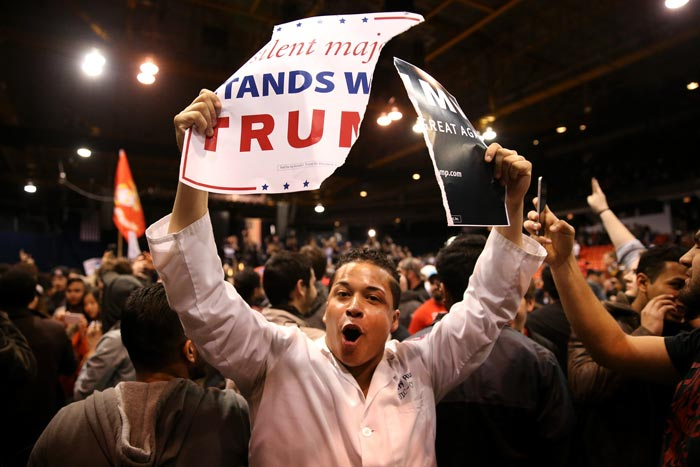 A protester shows off ripped Donald Trump campaign signs after it was announced the rally for the Republican presidential candidate was cancelled at the UIC Pavilion in Chicago on Friday, March 11, 2016. (Chris Sweda/Tribune News Service)