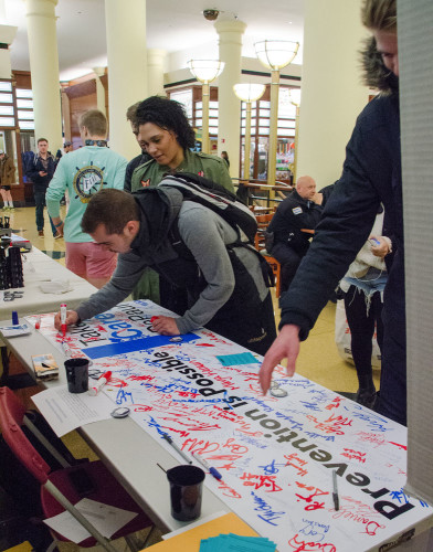 "Students sign a banner in solidarity in an event for sexual assault prevention called ""It's On Us"" Thursday. (Joseph Lu / The DePaulia)"