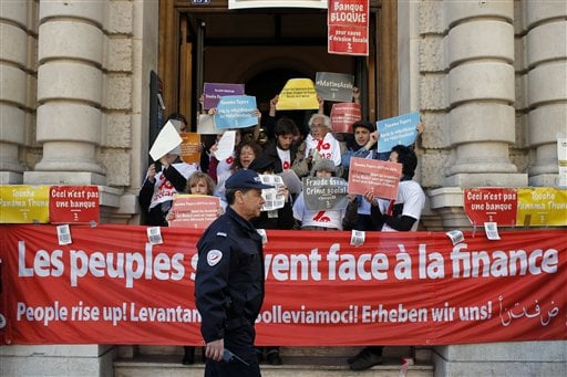 "French police officer walks by as anti-fraud activists are blocking entrances at Societe Generale's Paris headquarters as part of a protest accusing the French bank of ties to the so-called ""Panama Papers"" in Paris, France, Thusday, April 7, 2016. Societe Generale denies any accusations of fraud and tax evasion and repeated in a statement its commitment to the fight against such activities. (AP Photo/Francois Mori)"