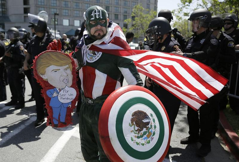 """Erik Lopez, dressed as """"Captain Mexico,"""" stands in front of police officers while protesting Republican presidential candidate Donald Trump outside of the Hyatt Regency hotel during the California Republican Party 2016 Convention. (Eric Risberg / AP)"""