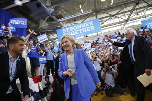 Democratic presidential candidate Hillary Clinton, followed by Sen. Bernie Sanders, I-Vt., arrives for a rally in Portsmouth, New Hampshire, Tuesday, July 12.
