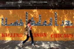 "A woman walks by the installation ""Killing Season Chicago"" on the outside of The Violet Hour in Wicker Park. The installation began in 2011. (Heather Charles 