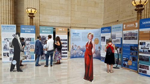 "Commuters at Union Station look upon ""Windy City in Motion: Movies + Travel in Chicago"" exhibit, a collaboration between DePaul University and Lake Forest College. (Photo Courtesy of Rachael Smith)"