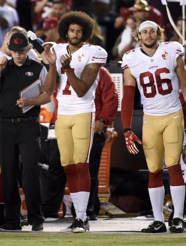 "San Francisco 49ers quarterback Colin Kaepernick applauds during the playing of ""God Bless America"" during the second half of an NFL preseason football game against the San Diego Chargers, Thursday, Sept. 1, 2016, in San Diego. (AP Photo/Denis Poroy)"