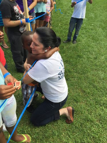 Mendoza hugs a child at the 49th Ward back to school picnic. (Brenden Moore/The DePaulia)