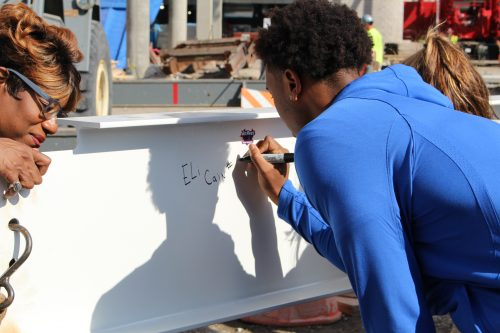 Sophomore guard Eli Cain signs his name on the final beam to be put up in the new DePaul arena on Oct. 5. (Jack Higgins/The DePaulia)