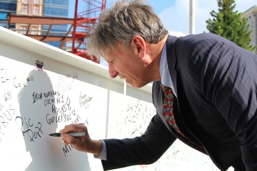 Head women's basketball coach Doug Bruno signs the final beam of the new arena to be placed in a ceremony on Wednesday. (Jack Higgins/The DePaulia)