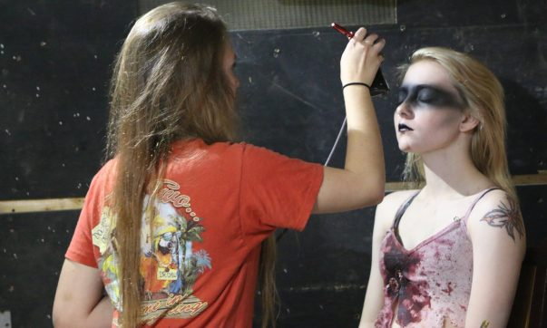 Makeup artists applying the finishing touches on actors.