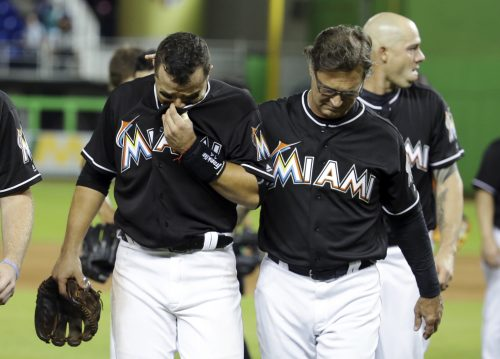 Miami Marlins' Martin Prado, left, walks off the field with manager Don Mattingly, right, after a baseball game against the New York Mets, Monday, Sept. 26, 2016, in Miami. The Marlins defeated the Mets 7-3. The Marlins pitcher Jose Fernandez was honored during the game. Fernandez was killed in a boating accident early Sunday. (AP Photo/Lynne Sladky)