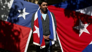A man stands before a Cuban and Chilean flag displayed outside Cuba's embassy in Santiago, Chile, Saturday, Nov. 26, 2016, the day after Fidel Castro's death. Castro, who led a rebel army to improbable victory, embraced Soviet-style communism and defied the power of 10 U.S. presidents during his half century rule of Cuba, died at age 90 in Cuba late Friday, Nov. 25. (Esteban Felix | AP Photo)