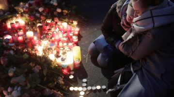 Two women mourn beside candles in Berlin, Germany, Tuesday, Dec. 20, the day after a truck ran into a crowded Christmas market nearby and killed several people. (Markus Schreiber   AP Photo)
