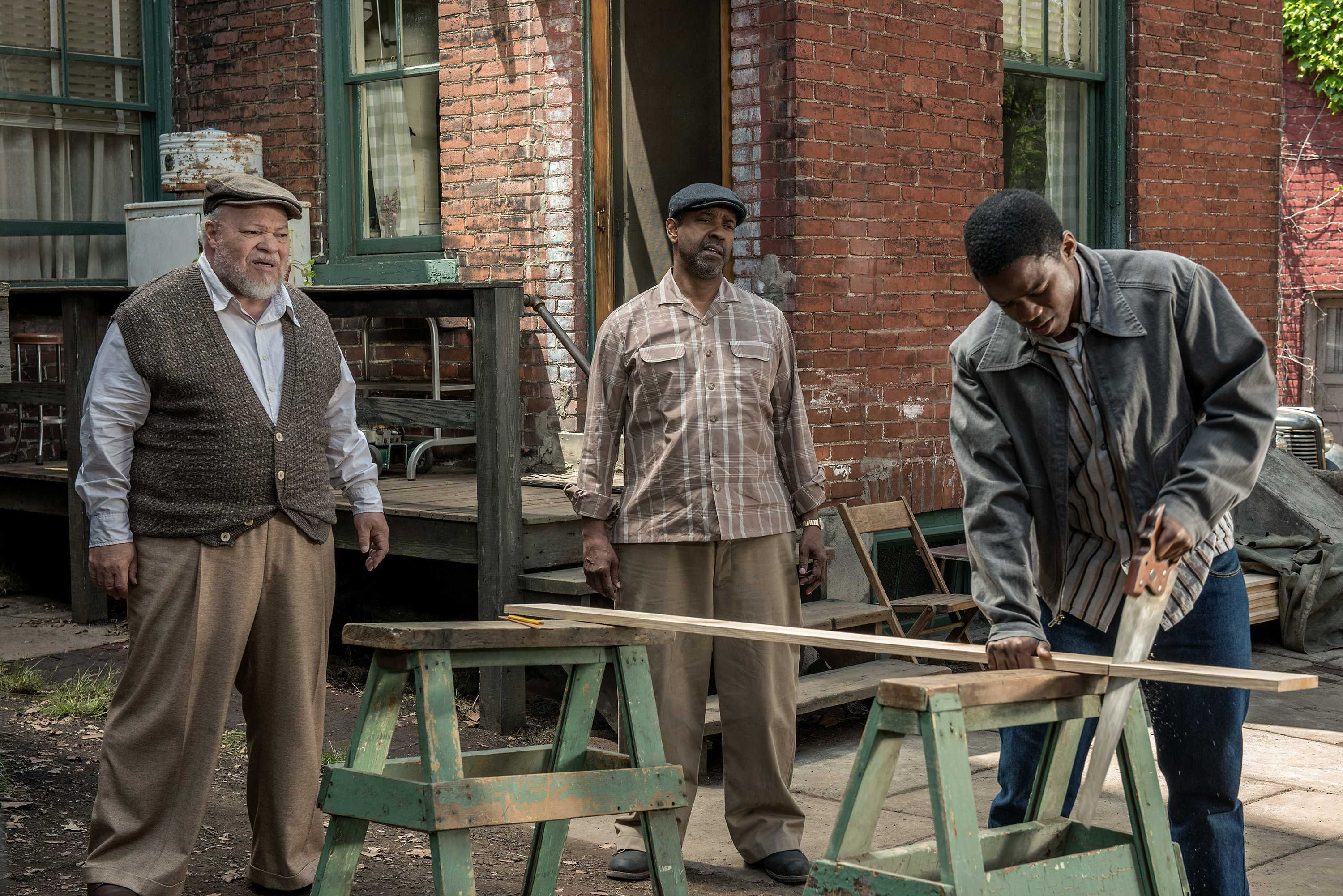 Denzel Washington (center) plays Troy Maxson, Stephen McKinley Henderson (left) plays Jim Bono and Jovan Adepo (right) plays Cory in the film