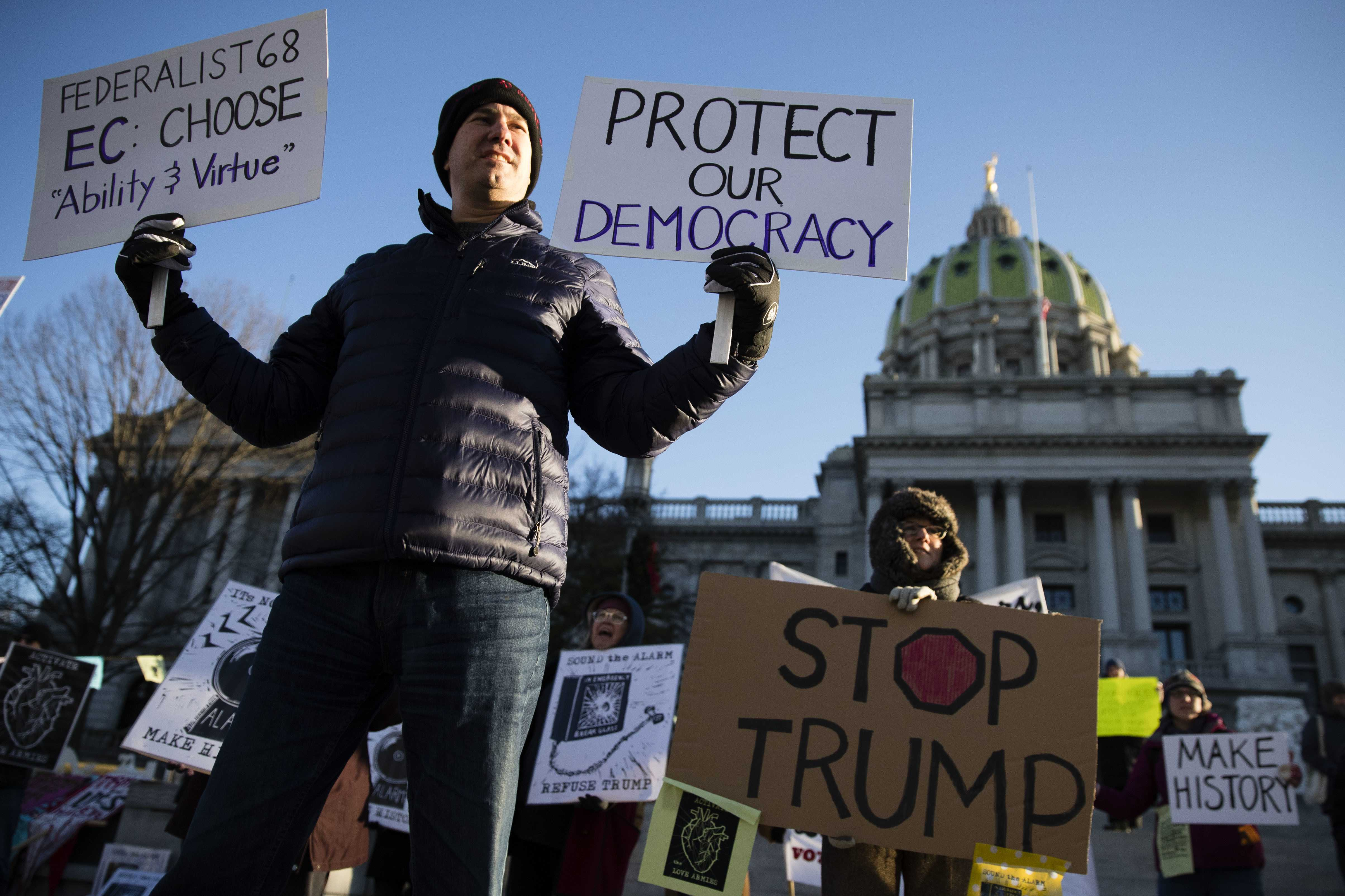 Protesters demonstrate ahead of Pennsylvania's 58th Electoral College at the state Capitol in Harrisburg, Pennsylvania, Monday, Dec. 19, 2016. The demonstrators were waving signs and chanting in freezing temperatures Monday morning as delegates began arriving at the state Capitol to cast the state's electoral votes for president. (Matt Rourke | AP Photo)