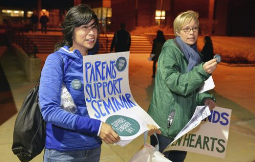 In this Feb. 20, 2017 photo, Iliana Mora and Amanda Nugent hand out signs and buttons in support of an upcoming all-school seminar on civil rights at New Trier High School before a school board meeting at the school's Northfield campus in Northfield, Ill. The school is holding a daylong seminar on civil rights designed to help students in the largely white and affluent school see things from other perspectives on Feb. 28. Conservative groups and some parents have raised concerns about the tone being too liberal. (Brian O'Mahoney/Chicago Tribune via AP)