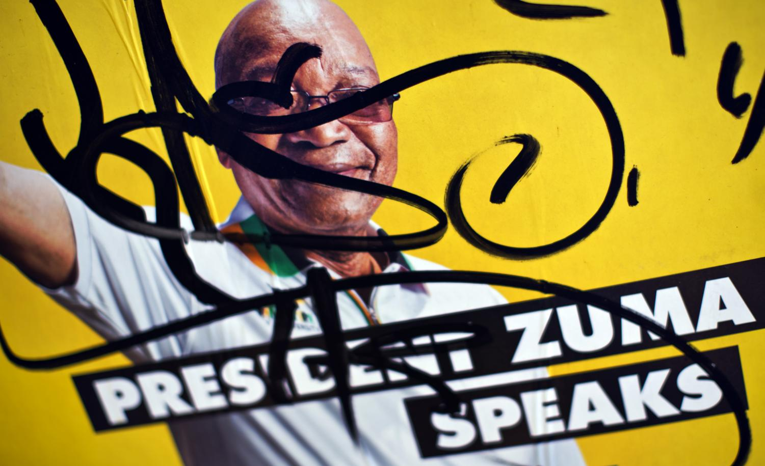 An election poster of former President Jacob Zuma is defaced in the downtown area of Johannesburg, South Africa in this May 2, 2014 photo. Zuma resigned after pressure from his party amid scandals that came up during his time in office. (Ben Curtis | Associated Press)