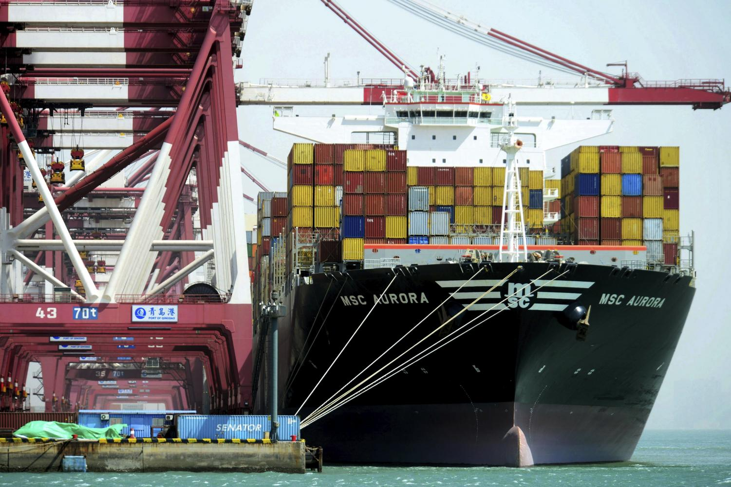 Containers are loaded onto a cargo ship at the port in Qingdao in east China's Shandong province. China vowed to fight the U.S.