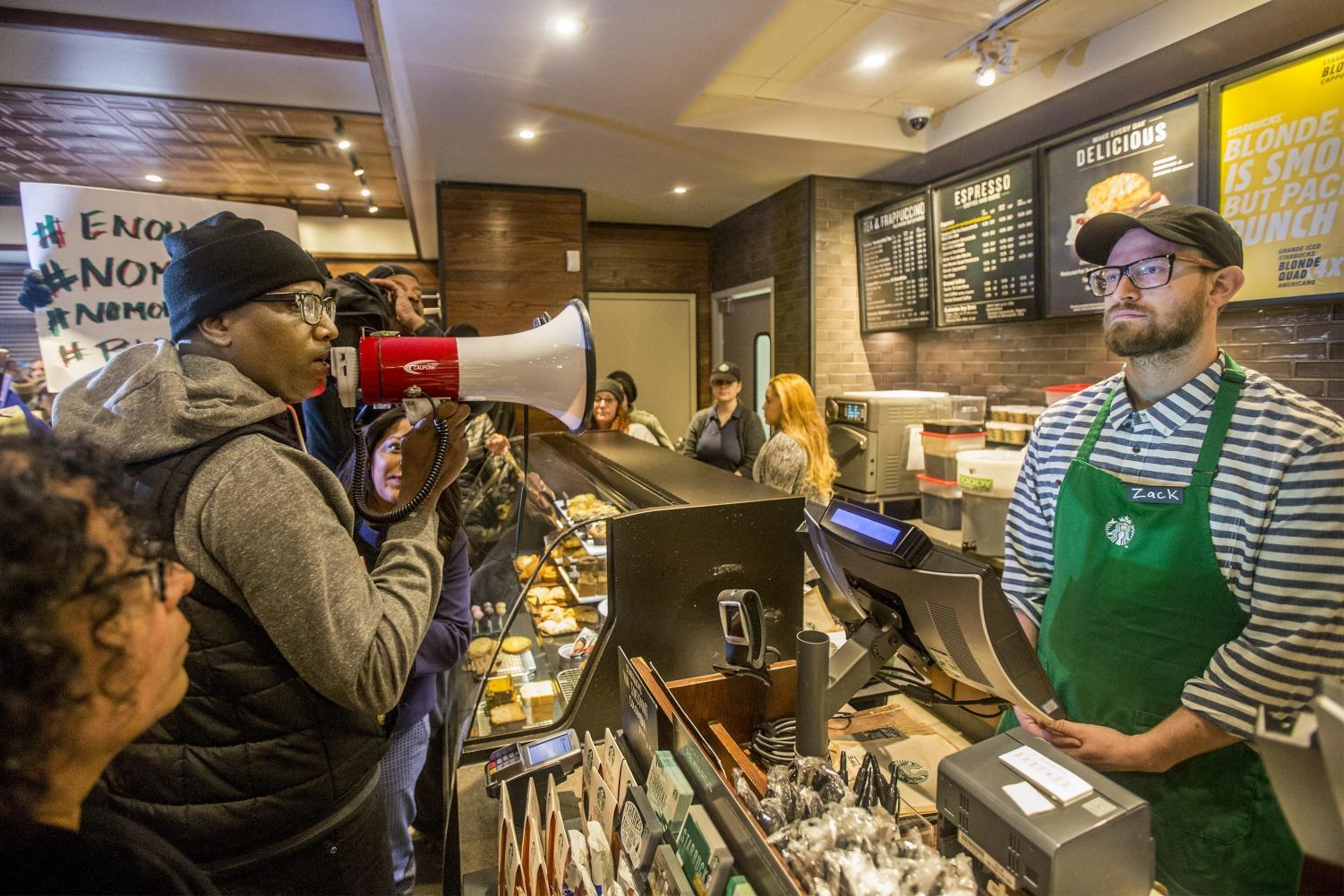 Activist Asa Khalif, left, stands inside a Starbucks, April 15 demanding the firing of the manager who called police resulting the arrest of two black men.  (Michael Bryant | The Philadelphia Inquirer via AP)