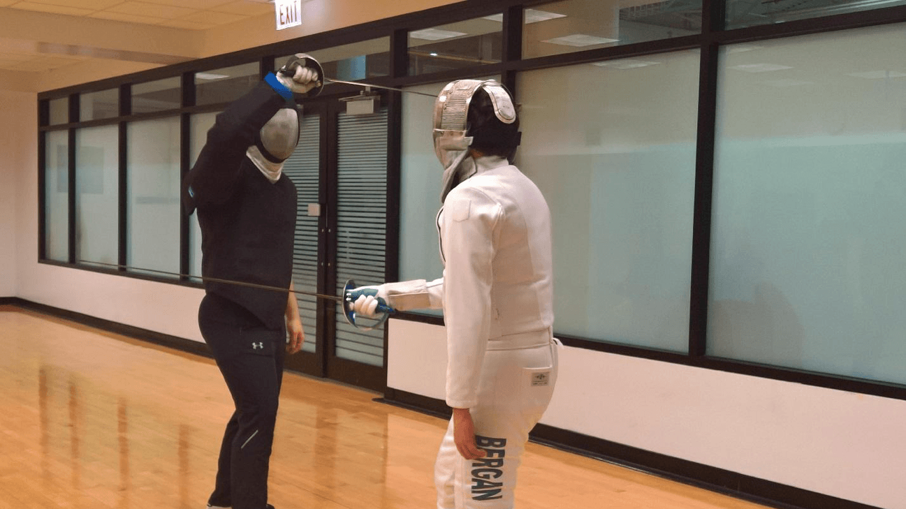 A fencer in a black suit practices fencing against a fencer in a white suit at an unspecified location in the Ray. (William Sullivan | The DePaulia)
