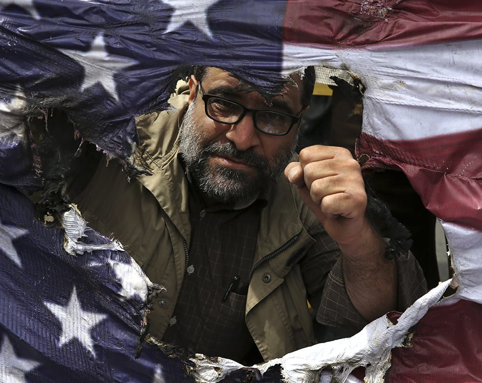 An Iranian protestor clenches his fist behind a burnt representation of the U.S. flag during a gathering after their Friday prayer in Tehran, Iran on May 11, 2018. Thousands of Iranians took to the streets in cities across the country to protest U.S. President Donald Trump's decision to pull out of the nuclear deal with world powers.