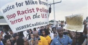 Missouri Highway Patrol Capt. Ron Johnson walks among people protesting the police shooting death of Michael Brown in Ferguson last month.