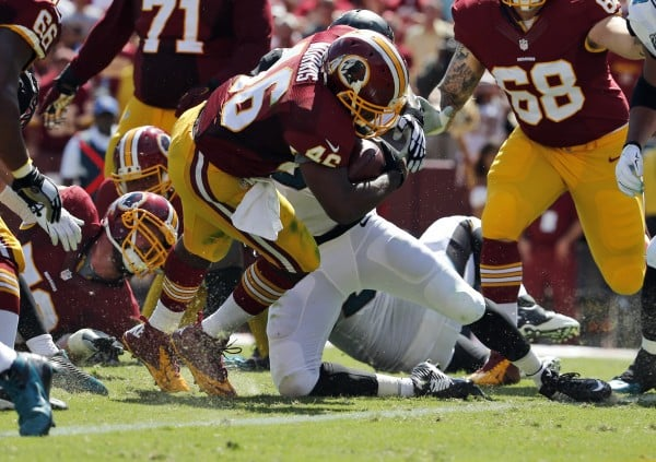 Washington Redskins running back Alfred Morris (46) scores a touchdown as he is hit by Jacksonville Jaguars linebacker Dekoda Watson (57) during the first half of an NFL football game Sunday, Sept. 14, 2014, in Landover, Md. (AP Photo/Evan Vucci)