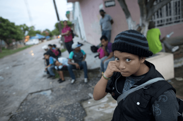 A 14-year-old Guatemalan girl traveling alone waits for a northbound freight train along with other Central American migrants, in Arriaga, Chiapas state, Mexico. More than 52,000 unaccompanied children have been apprehended since October. (AP Exchange)