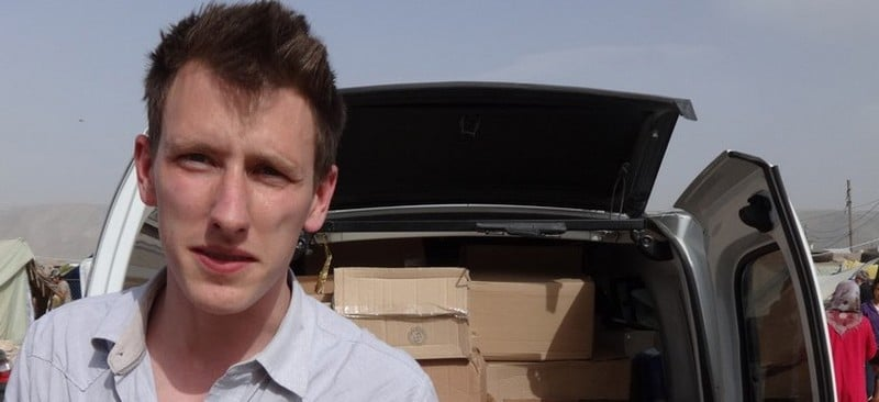 This undated photo provided by Kassig Family shows Peter Kassig standing in front of a truck filled with supplies for Syrian refugees. Confronted by terrorists beheading Americans, President Barack Obama has ordered a review of how the United States responds when citizens are taken hostage overseas. (AP Photo/Courtesy Kassig Family)