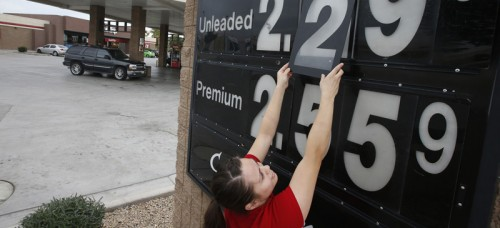 Quick Trip clerk Roxana Valverde adjusts the gas price sign numbers at a QT convenient store in Tolleson, Arizona. Gas prices continue to tumble nationwide. (Ross D. Franklin | AP)