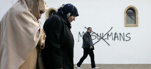 French Muslims walk past anti-Muslim graffiti painted on a Mosque in Saint-Etienne, France. (Laurent Cipriani | AP)