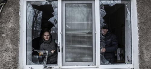 Residents peer out of a home hit by artillery amid renewed violence near the Eastern Ukrainian city of Donetsk. Jaresko's responsibilities include managing the financial burden of Ukraine's defense. (Manu Brabo | AP)