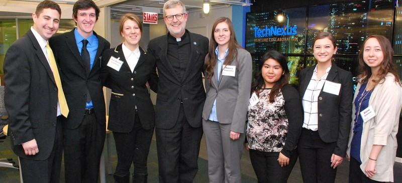 Rev. Dennis H. Holtschneider (center) poses with (L-R) Adam H. Grossman, David Allen, Sue Nicole Susenburger, Monica Grygorowiz, Jenny Fuerte, Morgan Schulhof, and Elaine Ackerman, the winners at the DePaul Student Innovation Awards. (Photo courtesy of Kathy Hillegonds at the Driehaus College of Business)