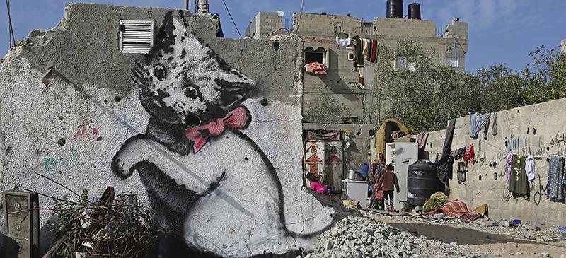 A Banksy-produced mural sits amid rubble in the Gaza Strip. (Adel Hana | AP)