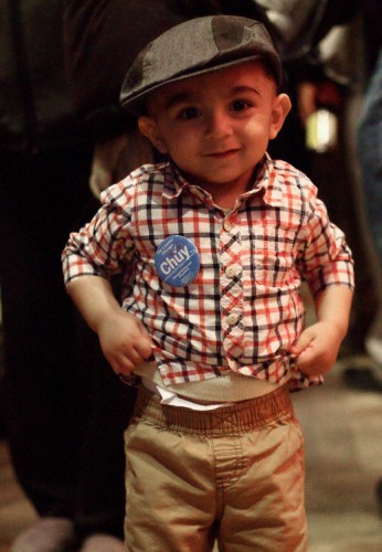 "One and a half-year-old Azan joined his father Assad Saadat at Jesus ""Chuy"" Garcia's election night event on Feb. 24. Supporters passed out buttons with Garcia's characteristic mustache among the dancing crowd at the Alhambra restaurant in the West Loop. (Megan Deppen / The DePaulia)"
