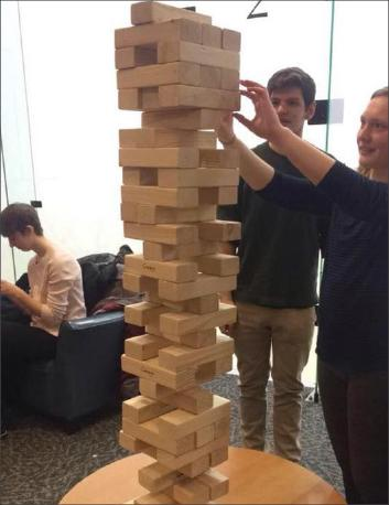 Students build a giant Jenga tower at the Ray Meyer Fitness Center and Recreation Thursday for Retro Sports Night. (Photo courtesy of Alyssa McHugh)