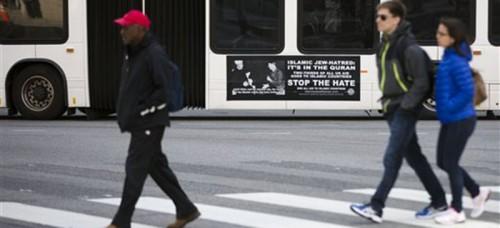 People walk past an anti-Muslim advertisement placed on a Philadelphia public bus. (AP Photo/Matt Rourke)