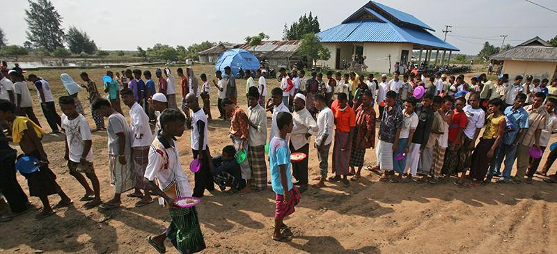 People wait for water at a refugee camp for Rohingyas, a persecuted Muslim minority group in Myanmar. (AP Photo/Binsar Bakkara)