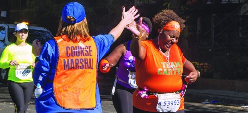 Nikki Carter, 42, of Chicago high fives a course marshall near mile 10 of the Bank of America Chicago Marathon. No matter the distance, it's important to take time to train for races. (Courtney Jacquin / The DePaulia)