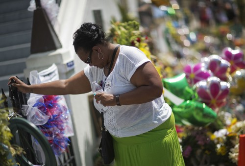 "Terri Barr, of Columbia, S.C., stands silently against a fence while visiting a sidewalk memorial in memory of the shooting victims in front of Emanuel AME Church Monday, June 22, 2015, in Charleston, S.C. ""It was just senseless and I just wanted to be here,"" said Barr. ""It's sad. It's hurting, but you know, we'll heal."" (AP Photo/David Goldman)"