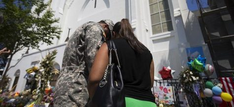 U.S. Army Spc. Ron Leary, left and Astride Leary, of Savannah, Ga., pray at a sidewalk memorial in memory of the shooting victims in front of Emanuel AME Church, Monday, June 22, 2015, in Charleston, S.C. (AP Photo/David Goldman)